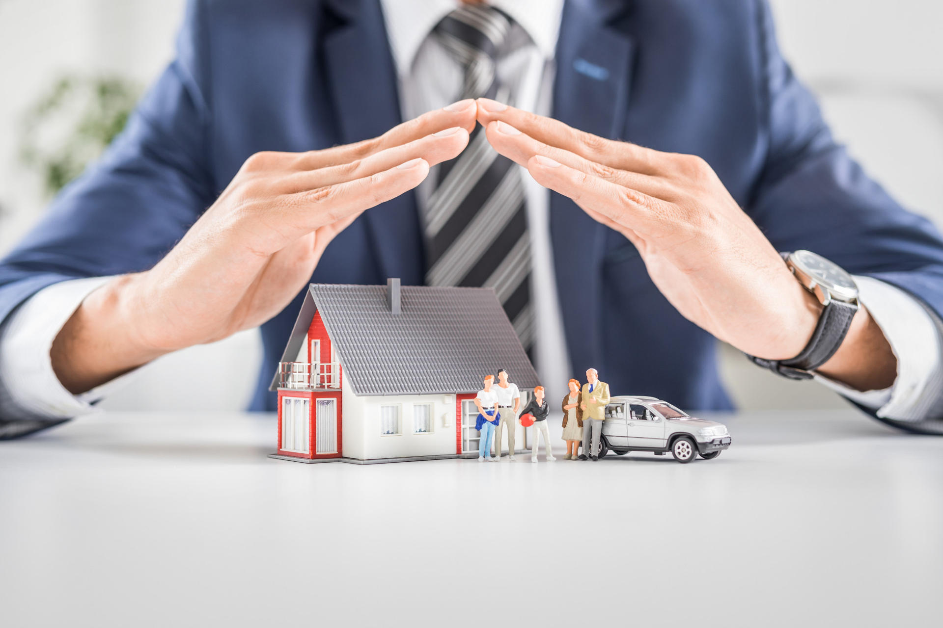 insurance broker with hands covering model house